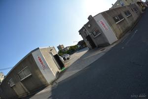 低い建物に囲まれた駐車場の出入口、対角線魚眼写真 AF DX Fisheye-Nikkor 10.5mm f/2.8G ED